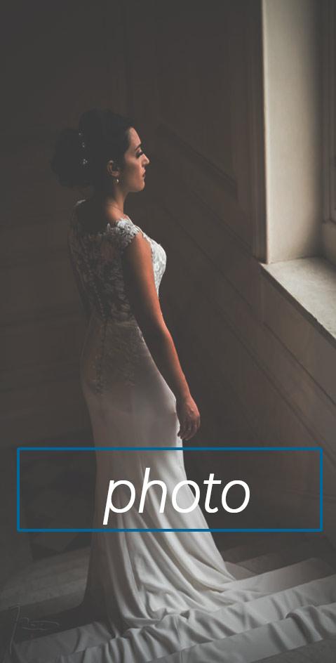 Photographe mariage paris. Une mariée à la fenêtre regarde le mariage dans le jardin