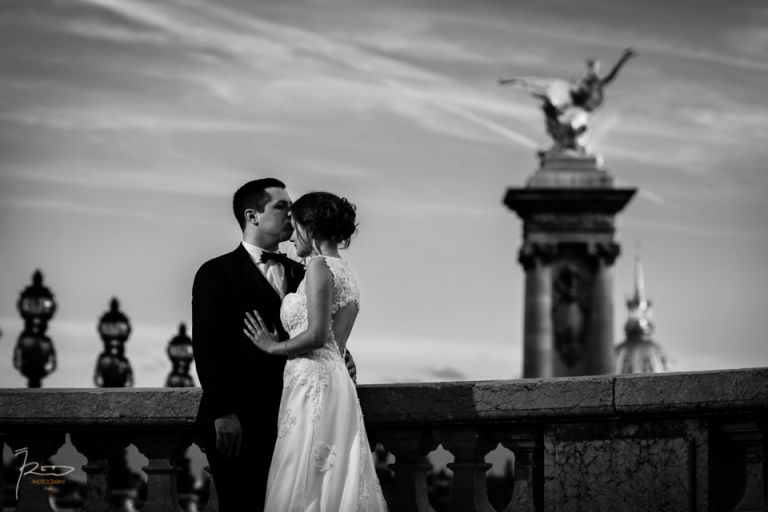 Un marié embrasse sa femme sur le front sur le pont Alexandre III à Paris durant une séance photo après le mariage.
